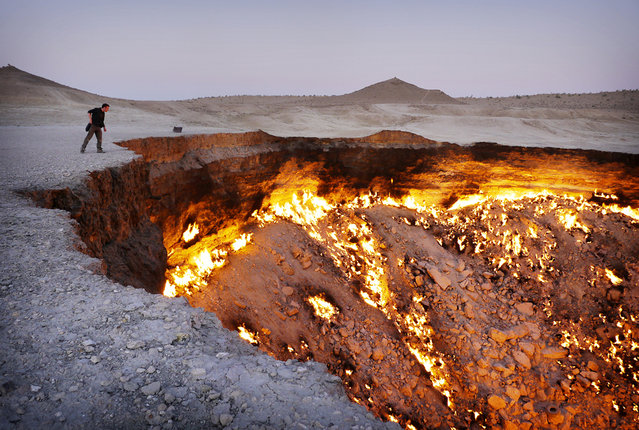 A vivid display of the country's huge gas reserves is the Darvaza gas crater. In the 1970s, Soviet engineers accidentally collapsed this cavern about 260 km north of Ashgabat, while exploring for gas in the Karakum Desert. The escaping methane was lit, intending to quickly burn it off and avoid poisoning nearby villages, but it has continued burning ever since. (Photo by Amos Chapple via The Atlantic)