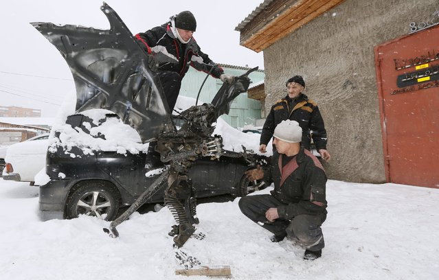 """Mechanic and welder Sergei Kulagin (top), 33, and his colleagues test """"The Animal"""", an electro-mechanical mobile iron robot made of car components, outside an automobile repair workshop in the Siberian town of Divnogorsk outside Krasnoyarsk, Russia, November 30, 2015. (Photo by Ilya Naymushin/Reuters)"""