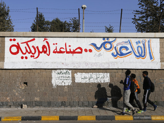"""People walk past a graffiti reading """"Al Qaeda is American-made"""" at the site of a recent car bomb attack in Sanaa January 14, 2015. (Photo by Khaled Abdullah/Reuters)"""