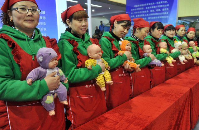 Maternity matrons demonstrate how to take care of babies during a skilled worker festival in Hefei, Anhui province, January 16, 2015. More than one hundred workers with various professions performed during the event, according to local media. (Photo by Reuters/Stringer)