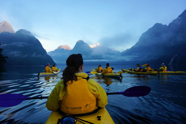 """Milford Sound Kayaking"". Kayaking Milford Sound in the South Island of New Zealand was the highlight of our trip. This photo captures the start of our journey with the sun just reaching the tops of the mountains, a few lingering clouds, the perfectly calm water, and one of the waterfalls cascading down the massive cliffs on both sides of the Sound. (Photo and caption by Daniel Furfari/National Geographic Traveler Photo Contest)"