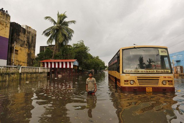 A boy wades next to a partially submerged bus in a flooded locality in Chennai, India, December 5, 2015. (Photo by Anindito Mukherjee/Reuters)