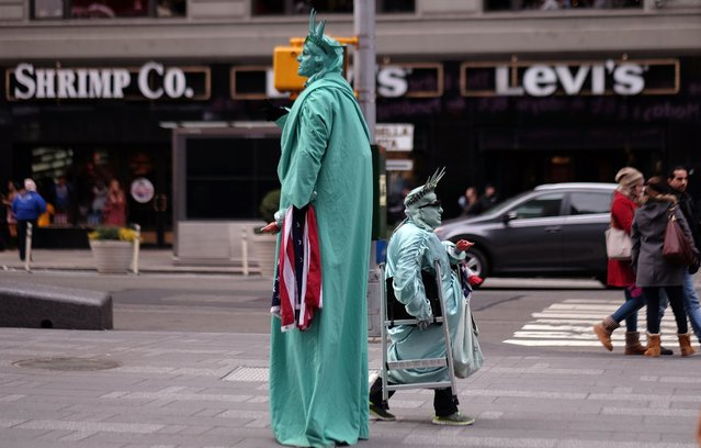 Two men dressed as the Statue of Liberty look for tourists to pose with them for pictures in exchange for donations in New York's Times Square on January 20, 2015. (Photo by Jewel Samad/AFP Photo)