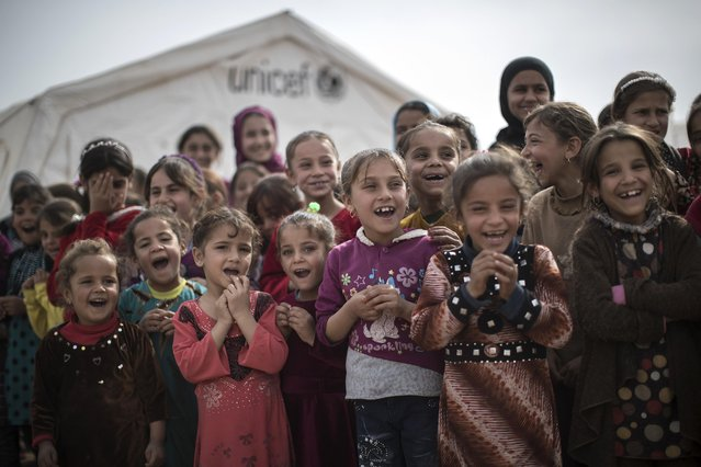 Iraqi children who were displaced by fighting in Mosul attend an outdoor class at a camp for internally displaced people in Hassan Sham, east of Mosul, Iraq, Thursday, November 10, 2016. The United Nations says over 34,000 people have been displaced from Mosul, with about three quarters settled in camps and the rest in host communities. (Photo by Felipe Dana/AP Photo)