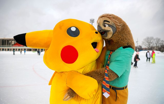 People dressed in costumes of Pokemon's Pikachu and Zootopia's sloth hug each other during a carnival devoted to St. Valentine's Day in Moscow, Russia on February 14, 2021. (Photo by Maxim Shemetov/Reuters)
