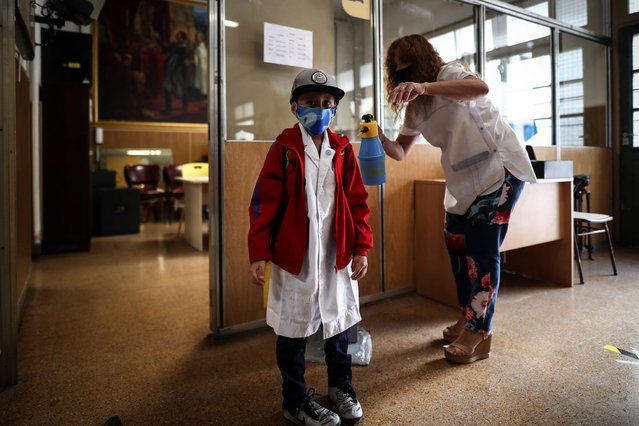 A worker disinfects a student at a school in Buenos Aires, Argentina, 17 February 2021. Student come back schools in Buenos Aires to and several other Argentinian provinces to begin a new school year almost a year after the teaching activities were suspended at classrooms due to coronavirus pandemic. (Photo by Juan Ignacio Roncoroni/EPA/EFE)