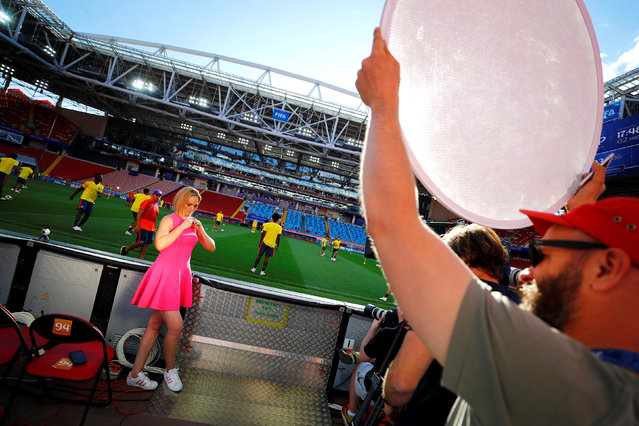 A TV presenter gets ready for her live-take during a training session of Colombia at the Spartak stadium in Moscow, Russia, July 2, 2018. As well as shooting all the matches, Reuters photographers are producing pictures showing their own quirky view from the sidelines of the World Cup. (Photo by Kai Pfaffenbach/Reuters)