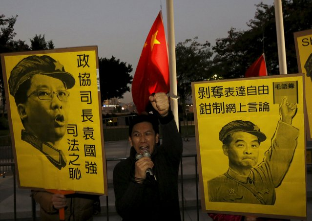 """Pro-democracy protesters against a copyright bill, which they say will restrict freedom of expression, carry placards depicting Hong Kong Chief Executive Leung Chun-ying (R) and Secretary for Justice Rimsky Yuen in front of a daily flag lowering ceremony outside Legislative Council in Hong Kong, China December 17, 2015. Chinese characters read """"Deprive freedom of expression. Suppress online opinion"""" (R) and """"The shame of justice"""". (Photo by Bobby Yip/Reuters)"""