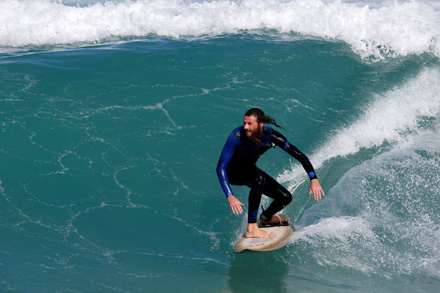 An ultra-Orthodox Jewish man surfs during a local competition in the Mediterranean Sea, near Ashdod, Israel November 17, 2016. (Photo by Amir Cohen/Reuters)