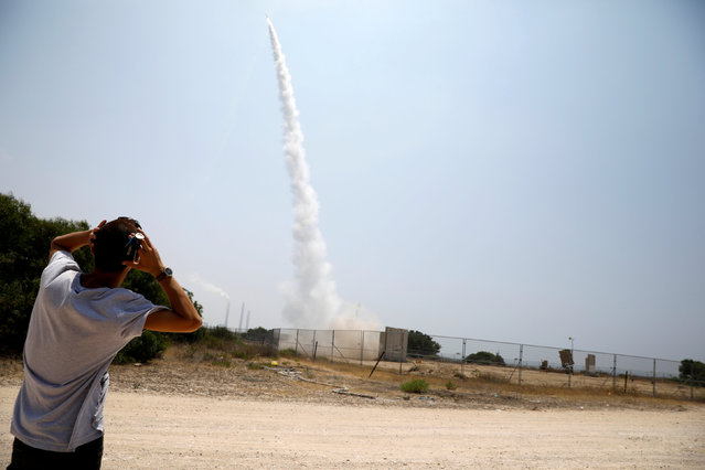 An Israeli man looks on as an Iron Dome launcher fires an interceptor rocket in the southern Israeli city of Ashkelon July 14, 2018. (Photo by Amir Cohen/Reuters)