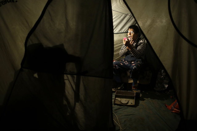 """In this July 8, 2018 photo, Santiago Astopilco puts on his clown make-up to play the part of """"Vaguito"""" inside his tent at the Tony Perejil circus set up in the shantytown of Puente Piedra on the outskirts of Lima, Peru. These days, Lima's circus acts find themselves increasingly pinched for space and money. (Photo by Martin Mejia/AP Photo)"""