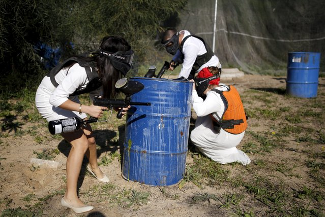 "Israeli couples attend a ""trash the dress"" event at a paint-ball venue in the southern Israeli city of Ashdod, December 25, 2015. Twelve Israeli couples wore their wedding outfits once again on Friday as they took part in a video clip where they deliberately ruined their wedding outfits, in keeping with the trendy wedding style photography dubbed ""trash the dress"". (Photo by Amir Cohen/Reuters)"