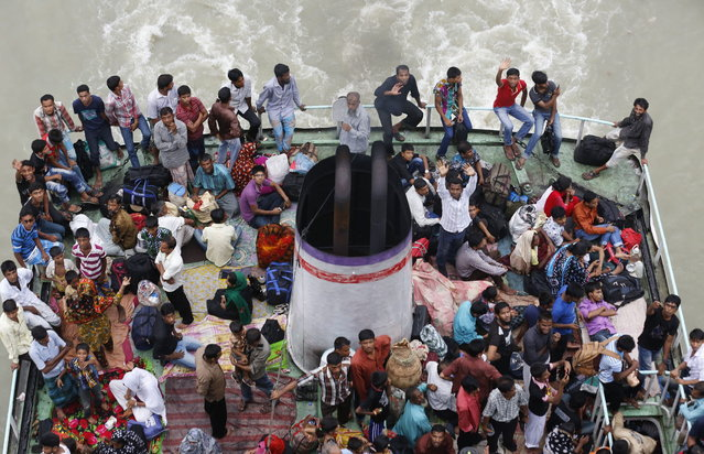 People look on from an overcrowded passenger boat navigating through the Buriganga River in Dhaka August 7, 2013. Millions of residents in Dhaka have started the exodus home from the capital city ahead of the Eid al-Fitr holiday, which marks the end of the fasting month of Ramadan. (Photo by Andrew Biraj/Reuters)