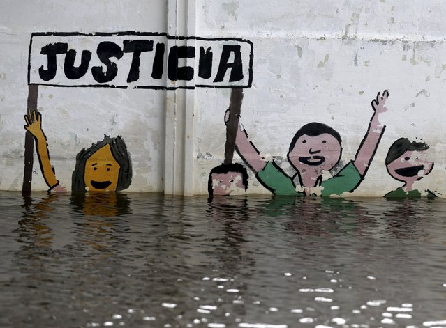 "Graffiti saying ""justice"" partially seen above flood waters in Asuncion, December 27, 2015. (Photo by Jorge Adorno/Reuters)"