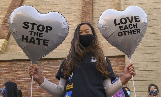 "In this March 13, 2021, file photo, Chinese-Japanese American student Kara Chu, 18, holds a pair of heart balloons decorated by herself for the rally ""Love Our Communities: Build Collective Power"" to raise awareness of anti-Asian violence outside the Japanese American National Museum in Little Tokyo in Los Angeles. The shootings at three Georgia massage parlors and spas Tuesday, March 16, that left eight people dead, six of them women of Asian descent, come on the heels of a recent wave of attacks against Asian Americans since the coronavirus first entered the United States. (Photo by Damian Dovarganes/AP Photo/File)"
