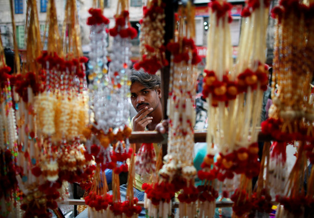 A street vendor is pictured through the garlands kept on sale for the Tihar festival, also called Diwali, along the streets of Kathmandu, Nepal, October 26, 2016. (Photo by Navesh Chitrakar/Reuters)