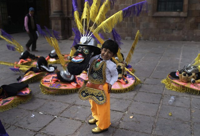 """In this Sunday, August 5, 2018 photo, 8-year-old Miguel smiles while posing in his """"rey moreno"""" or """"black king"""" dance costume before the start of a procession honoring Our Lady of Copacabana, in Cuzco, Peru. The black king, one of the many characters that make up the """"Morenada"""" or Dance of the Black Slaves, often wears a mask with exaggerated features and a tongue hanging out to symbolize the exhaustion of the slaves from the hard work and high altitudes, some believe. (Photo by Martin Mejia/AP Photo)"""