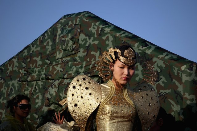 A model in Mongolia costumes prepares backstage after a Mongolian ritual ceremony in Xiangshawan Desert, also called Sounding Sand Desert on July 19, 2013 in Ordos of Inner Mongolia Autonomous Region, China. Xiangshawan is China's famous tourist resort in the desert. It is located along the middle section of Kubuqi Desert on the south tip of Dalate League under Ordos City. Sliding down from the 110-metre-high, 45-degree sand hill, running a course of 200 metres, the sands produce the sound of automobile engines, a natural phenomenon that nobody can explain. (Photo by Feng Li/Getty Images)