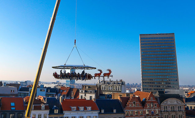 "Guests enjoy dinner at the table ""Santa in the sky"", lifted by a crane and decorated to match the appearance of a ""Santa Sleigh"" as part as the Christmas festivities, in Brussels, Belgium, November 25, 2016. (Photo by Yves Herman/Reuters)"