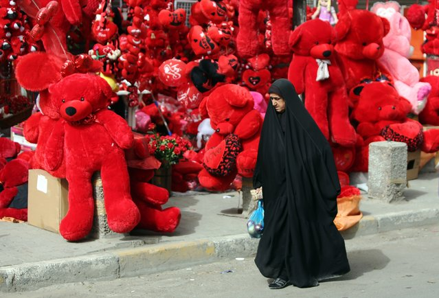 An Iraqi woman walks past a shop displaying red teddy bears in preparation for Valentine's day in Baghdad's Karrada district on February 12, 2014. (Photo by Ahmad Al-Rubaye/AFP Photo)