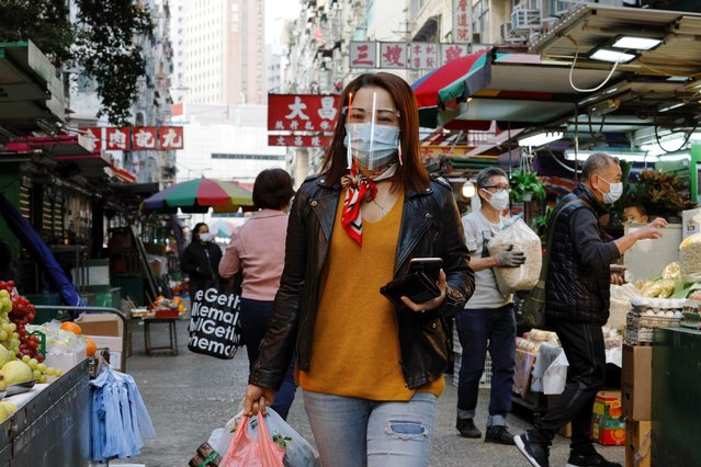 A resident wears a face mask and a shield as she walks at a wet market at Jordan residential area, in Hong Kong, China on January 22, 2021. (Photo by Tyrone Siu/Reuters)