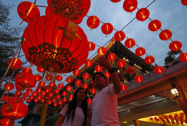 "A couple takes a ""selfie"" with decorations at a temple, ahead of the Chinese Lunar New Year celebrations in Nonthaburi province, on the outskirts of Bangkok February 18, 2015. (Photo by Chaiwat Subprasom/Reuters)"
