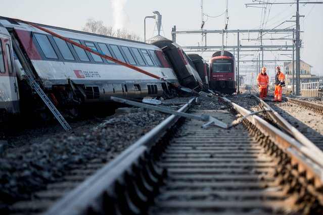 Rescue service men and firemen work at a derailed train a the accident site in Rafz, canton Zurich, Switzerland, on Friday, February 20, 2015. The collision of two passenger trains in the early morning caused five injured, one of them severe, police said. (Photo by Ennio Leanza/AP Photo/Keystone)
