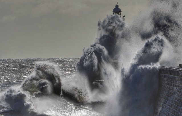 Waves from the North Sea crash against the Tynemouth Lighthouse on the north east coast of England, where cold winds have brought freezing temperatures on Monday April 5, 2021. Recent warm weather has changed as temperatures have dropped significantly with snow falling in some areas and high winds sweeping across the country. (Photo by Owen Humphreys/PA via AP Photo)