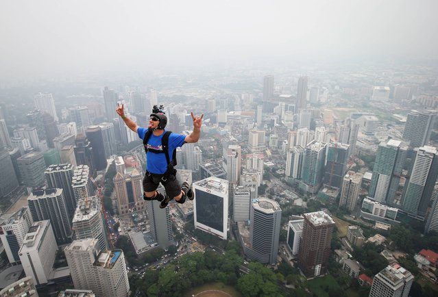 Base jumper Kieran Francis Tomlinson of Australia leaps from the 300-meter Open Deck of the Malaysia's landmark Kuala Lumpur Tower during the International Tower Jump in Kuala Lumpur, Friday, September 27, 2013. About 103 professional base jumpers from 20 countries took part in the annual event. (Photo by Vincent Thian/AP Photo)