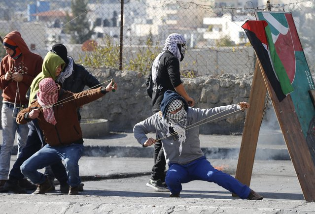 Palestinian protesters use slingshots to hurl stones towards Israeli troops during clashes in the West Bank city of Bethlehem January 13, 2016. (Photo by Ammar Awad/Reuters)