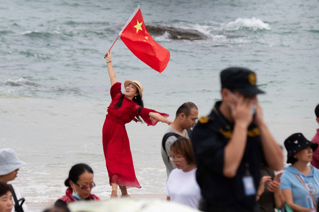 A woman holds up the Chinese national flag as people gather to watch the the launch of the Long March 5B rocket carrying China's Tianhe space station core module from the Wenchang Spacecraft Launch Site in Hainan Province, China, 29 April 2021. China launched into space the core module of its space station, marking the beginning of a series of launch missions to complete the space station by the end of next year. (Photo by Matjaz Tancic/EPA/EFE)