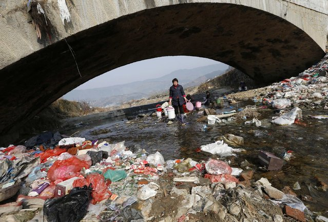 Villagers wash clothes in the garbage-filled Shenling River, in Yuexi county, Anhui province, February 14, 2015. (Photo by William Hong/Reuters)