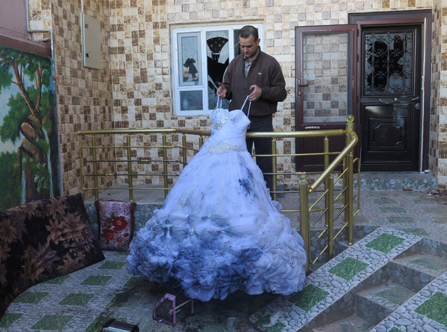 Ahmed Hassan Majid, a Shiite Turkmen, holds the only wedding dress which survived the torching of his house and bridal shop during a wave of Kurdish-Turkmen violence, in the northern Iraqi town of Tuz Khurmatu, on December 8, 2015. Majid's house was torched when an incident between security forces at a checkpoint sparked a wave of violence in Tuz Khurmatu between the town's Turkmens and Kurds on November 12 who fight the same jihadist enemy but in areas where their front lines meet, the autonomous Kurdish region and the Baghdad-backed Shiite paramilitary forces are vying for influence. (Photo by Jean Marc Mojon/AFP Photo)