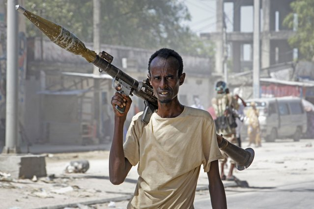 A soldier supporting anti-government opposition groups carries a rocket-propelled grenade launcher on a street in the Fagah area of Mogadishu, Somalia Sunday, April 25, 2021. Gunfire was exchanged Sunday between government forces loyal to President Mohamed Abdullahi Mohamed, who signed into law on April 14 a two year extension of his mandate and that of his government, and other sections of the military opposed to the move and sympathetic to former presidents Hassan Sheikh Mohamud and Sharif Sheikh Ahmed. (Photo by Farah Abdi Warsameh/AP Photo)