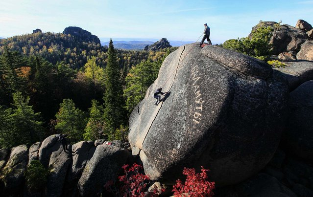 """A tourist climbs up to reach the top of the rock named """"The Fourth Stolb"""" (the Fourth Pillar) at the Stolby National Reserve outside Krasnoyarsk, Russia, on October 2, 2013. (Photo by Ilya Naymushin/Reuters)"""