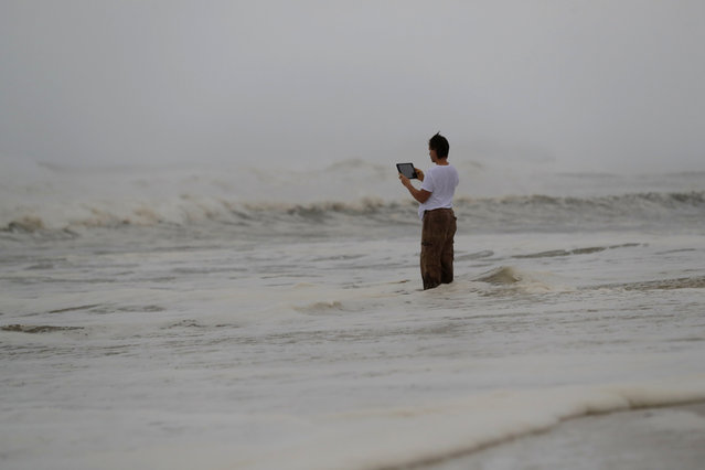 Peter Malave records the surf from encroaching Hurricane Michael, which is expected to make landfall today, in Panama City Beach, Fla., Wednesday, October 10, 2018. The hurricane center says Michael will be the first Category 4 hurricane to make landfall on the Florida Panhandle. (Photo by Gerald Herbert/AP Photo)