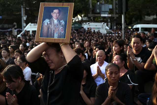 A woman cries while holding up a portrait of Thailand's King Bhumibol Adulyadej while his body is being moved from the Bangkok hospital where he died to the Grand Palace, in Bangkok, Thailand, October 14, 2016. (Photo by Athit Perawongmetha/Reuters)