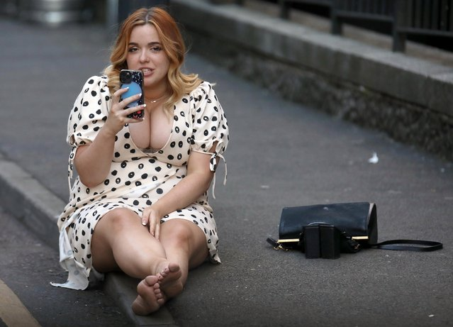 One woman was pictured sitting bare foot on a pavement in Leeds in the northern English county of Yorkshire on May 30, 2021. With the sun streaming down, Brits have been taking full advantage of the three-day weekend by packing out pub gardens and lining up the beers at bars. (Photo by Nb press ltd)