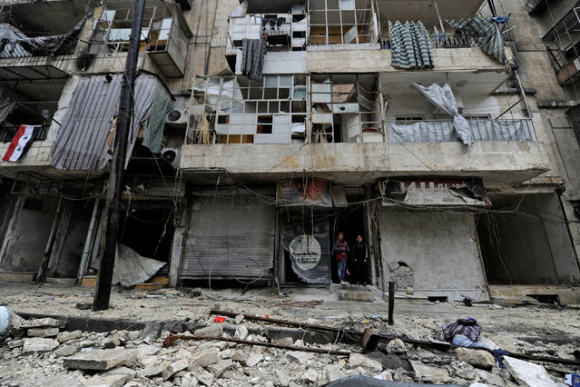 Boys stand amid the damage in the government-held al-Shaar neighborhood of Aleppo, during a media tour, Syria December 13, 2016. (Photo by Omar Sanadiki/Reuters)