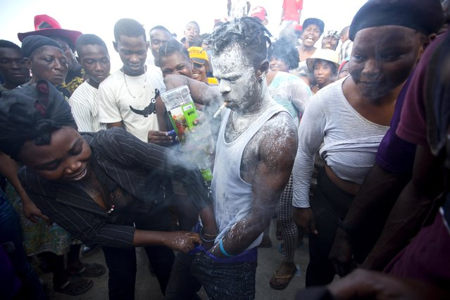 In this November 2, 2018 photo, a voodoo believer who is supposed to be possessed with Gede spirit performs rituals near Baron Samedi's tomb during the annual Voodoo festival Fete Gede at Cite Soleil Cemetery in Port-au-Prince, Haiti. As a proof that they got into trance and their bodies got possessed by Gedes, they drink and wash their faces, their eyes and even their genitals with a mixture of raw rum and hot chili peppers that, according to believers, could burn the skin of any human alive. (Photo by Dieu Nalio Chery/AP Photo)