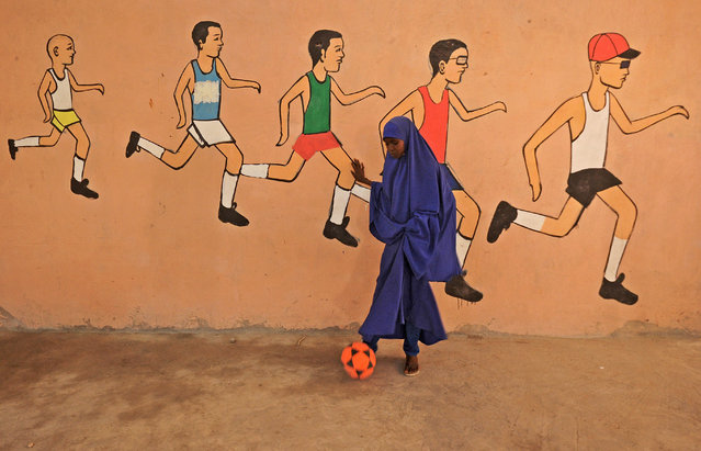 A school pupil kicks a ball during a sports lesson at a school in Mogadishu on December 6, 2016. (Photo by Mohamed Abdiwahab/AFP Photo)