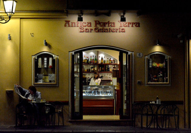 """Jill Sett, July winner. """"Piazza Garibaldi, Cefalu, Sicily. My favourite bar with Marcella the waitress staring off into space"""". MICK RYAN, JUDGE:Wandering around when travelling, especially off the beaten track, is a way to get a real feel for a place. Take a camera and you observe and enjoy more. Good street photography is hard, especially in daylight. When the sun sets and the lights are turned down you are hidden and less self-conscious. Use a high ISO and hand hold, and you may get something like this moment, where there is mystery and tension. (Photo by Jill Sett/The Guardian)"""