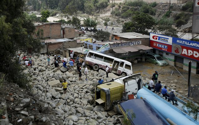 People look at trucks and cars stuck in the mud and stones after a landslide at the Carretera Central highway in Chosica, March 24, 2015. (Photo by Mariana Bazo/Reuters)