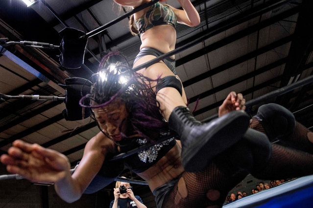 Professional wrestler Aria Palmer (top) kicks wrestler Gia Scott through the ropes during Autumn Armageddon 2018 in Galena, Maryland on October 6, 2018. (Photo by Jim Watson/AFP Photo)