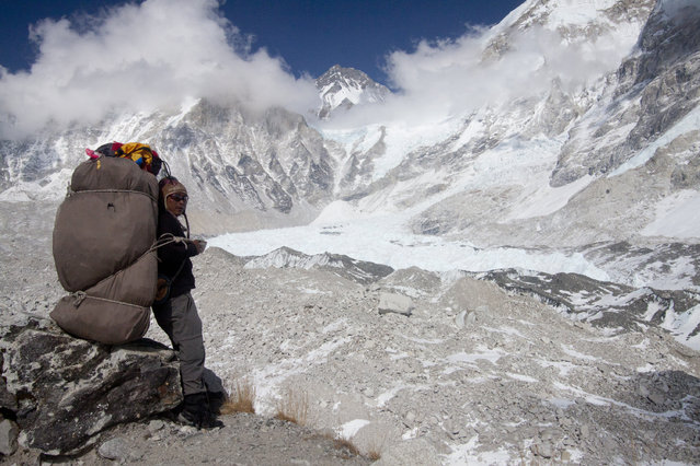 In this  Saturday, March 21, 2015 photo, a porter rests carrying supplies for the upcoming climbing season, near the Everest Base camp, Nepal. (Photo by Tashi Sherpa/AP Photo)
