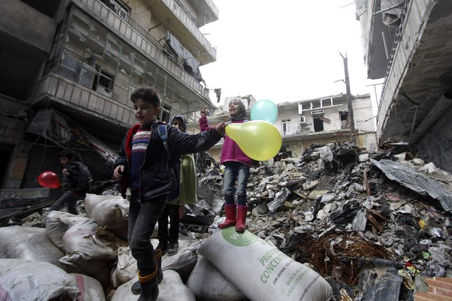 Schoolchildren stand on debris and carry balloons as they are gathering to express solidarity ahead of the International Childhood Cancer Day in Karm al-Jabal neighbourhood of Aleppo February 4, 2015. (Photo by Hosam Katan/Reuters)