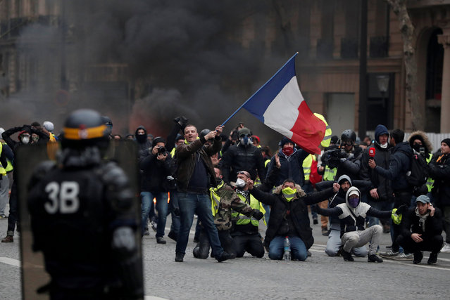 "A protester waves a French flag during clashes with police at a demonstration by the ""yellow vests"" movement in Paris, France, December 8, 2018. (Photo by Benoit Tessier/Reuters)"