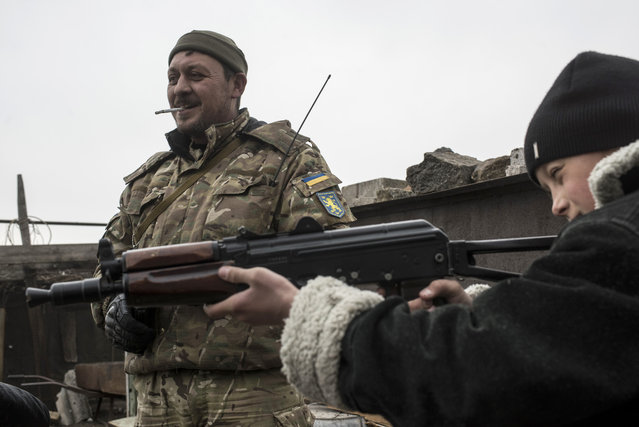 In a picture taken on Thursday, February 26, 2015, Tolik Tokar aims an assault rifle, given to him by an Ukrainian serviceman in the village of Chermalyk, eastern Ukraine. (Photo by Evgeniy Maloletka/AP Photo)
