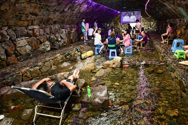 Tourists enjoy cool water in a cave in summer on July 14, 2021 in Jinhua, Zhejiang Province of China. (Photo by Hu Xiaofei/VCG via Getty Images)