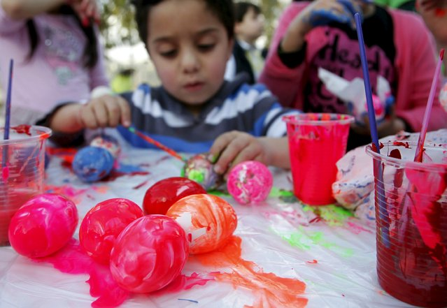 A boy paints eggs ahead of Easter celebrations in Abra April 4, 2015. (Photo by Ali Hashisho/Reuters)